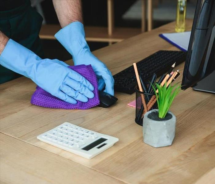 Worker disinfecting items on office desk