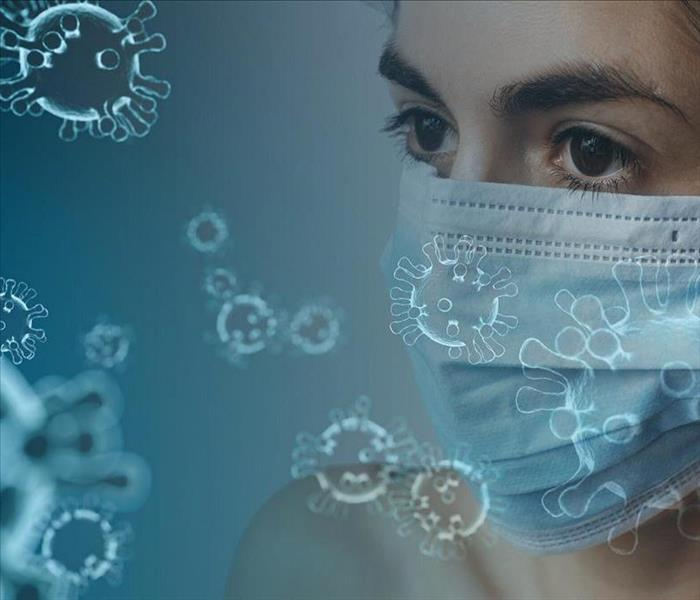 women with facial mask surrounded by graphic symbols of coronavirus