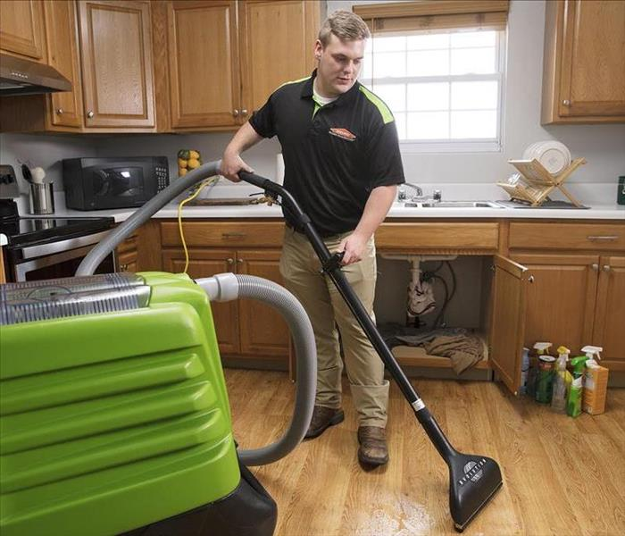 SERVPRO technician using water extraction wand
