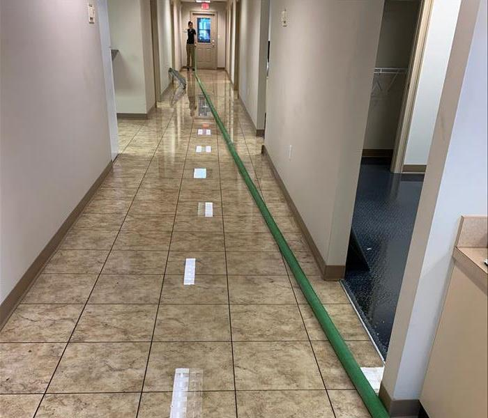 Photo showing water on floor of a long hallway with SERVPRO tech performing extraction
