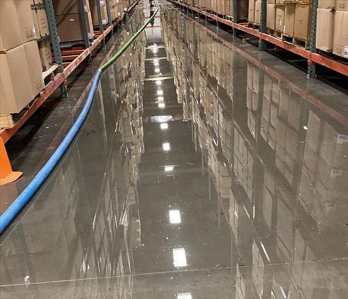 flooding and standing water in a warehouse near Jacksonville airport with a technician extracting water